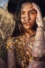 Портрет молодої жінки носять Літнє плаття з квітковим дизайном і капелюх сидять у кукурудзяному полі — стокове фото