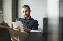 Бизнесмен сидит в офисе с поднятыми ногами и использует планшет — стоковое фото