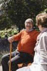 Seniorenpaar sitzt auf Bank im Park, redet und lacht — Stockfoto