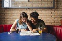Sorridente giovane coppia seduta a tavola in un caffè con mappa — Foto stock