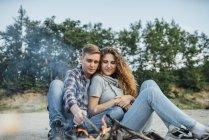 Романтическая пара, сидящая у костра на природе — стоковое фото