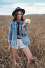 Portrait of laughing young woman wearing hat and denim jacket standing in a corn field with camera — Stock Photo