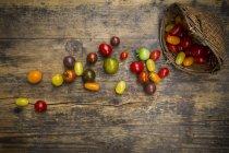 Herencia de tomates y canasta de mimbre sobre madera - foto de stock