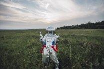 Космонавт валяет дурака на зеленом лугу — стоковое фото