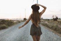 Visão traseira da jovem caminhando na estrada rural à noite — Fotografia de Stock