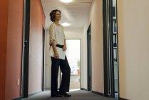 Empresária de pé no corredor do escritório, segurando laptop — Fotografia de Stock