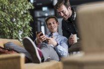 Dois colegas compartilhando celular no lounge do escritório — Fotografia de Stock