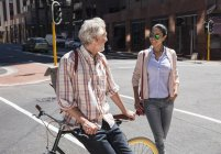 Mature homme avec vélo réunion femme en ville — Photo de stock