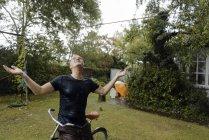 Зрелый человек с велосипедом наслаждается летним дождем в саду — стоковое фото