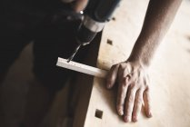 Close-up of carpenter using drill on piece of wood in workshop — Stock Photo