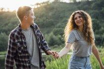 Романтическая пара, развлекающаяся на природе, держась за руки — стоковое фото