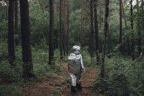 Spaceman explorando la naturaleza, caminando en el bosque - foto de stock