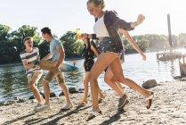 Grupo de amigos felizes se divertindo na beira do rio — Fotografia de Stock
