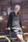 Зріла людина в місті спираючись на велосипеді перед будівлею — стокове фото