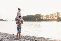 Giovane uomo che porta la ragazza sulle spalle alla riva del fiume — Foto stock