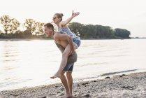 Young man giving girlfriend piggyback ride at riverbank — Stock Photo