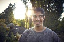 Портрет молодого человека в парке на закате солнца, улыбающегося — стоковое фото