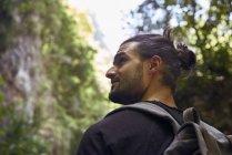 Вид сзади на самца туриста в лесу, оглядывающегося вокруг — стоковое фото