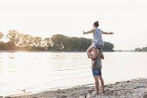 Un jeune homme fait une balade de piggyback avec une copine au bord d'une rivière — Photo de stock
