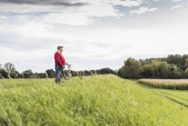 Senior man with bicycle in rural landscape — Stock Photo