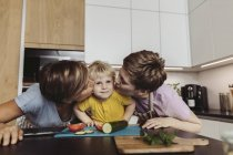 Happy lesbian couple kissing their child in kitchen — Stock Photo