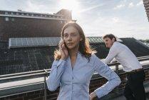 Деловые люди стоят на балконе, женщина разговаривает по телефону — стоковое фото