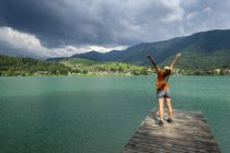 Teenager standing on wooden jetty, raised arms — Stock Photo