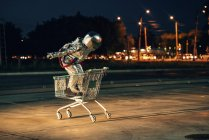 Spaceman in city at night on parking lot standing inside shopping cart — Stock Photo