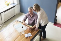 Mature couple with documents and tablet at home — Stock Photo