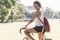 Портрет улыбающейся молодой женщины на велосипеде в парке — стоковое фото