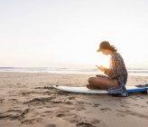 Молодая женщина сидит на доске для серфинга на пляже, используя смартфон — стоковое фото