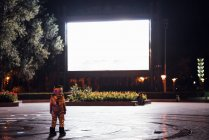 Spaceman standing on square at night attracted by shining projection screen — Stock Photo