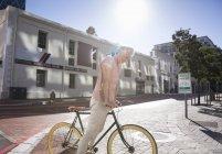 Hombre alegre maduro de pie con la bicicleta en la ciudad - foto de stock