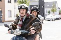 Heureux couple de personnes âgées équitation scooter moteur — Photo de stock