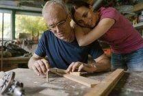 Mature woman watching man working in workshop — Stock Photo