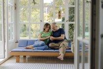 Cariñosa pareja madura sentada en el sofá en casa - foto de stock