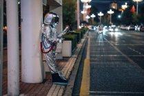 Spaceman de pie en la parada de autobús por la noche y sosteniendo el teléfono celular - foto de stock