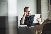 Бізнесмен сидить в офісі з ногами і за допомогою планшета — стокове фото