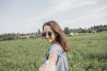 Mulher sorridente usando óculos de sol segurando a mão do parceiro no campo rural — Fotografia de Stock