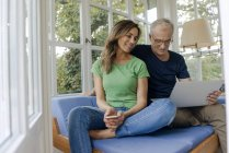 Smiling mature couple sitting on couch at home sharing laptop — Stock Photo