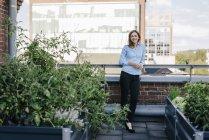 Businesswoman standing on her urban rooftop garden — Stock Photo