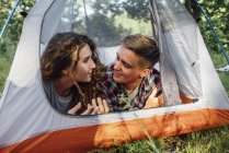 Happy young couple lying in tent in nature and talking — Photo de stock