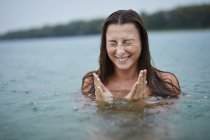 Portrait of freckled young woman bathing in lake on rainy day — Stock Photo