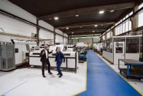 Manager and skilled worker dancing in factory workshop, having fun — Stock Photo