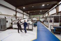 Менеджер и квалифицированный работник танцы в мастерской завода, весело — стоковое фото