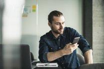 Молодой бизнесмен сидит в офисе, используя мобильный телефон — стоковое фото