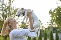 Mulher feliz segurando cão vestindo uma gravata ao ar livre — Fotografia de Stock