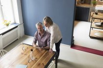 Mature couple using tablet at home — Stock Photo