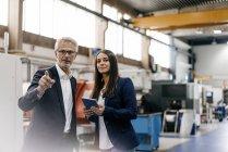 Homme d'affaires et femme d'affaires dans une entreprise de haute technologie, ayant une réunion dans un atelier d'usine — Photo de stock