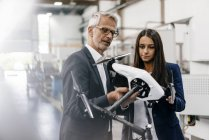 Businessman and businesswoman in high-tech enterprise, discussing production of drones — Stock Photo